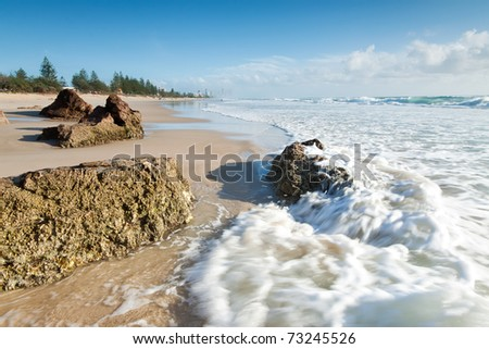 australian seascape with rushing wave in foreground (miami beach,qld,australia) - stock photo