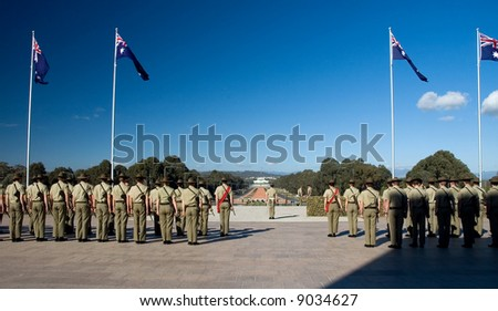 australian soldiers standing, waving australian flags, Canberra Parliament House in background - stock photo