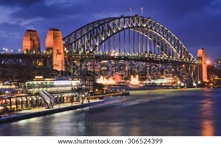 Australian Sydney Harbour bridge side view at sunset from Circular quay highly illuminated with lights reflecting in blurred harbour waters - stock photo