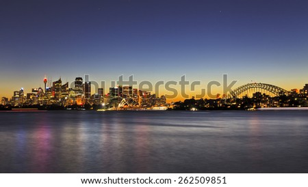 Australian Sydney landmarks - and harbour bridge at sunset in panoramic view when bright city lights reflecting in harbour water - stock photo