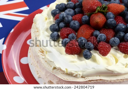 Australian traditional dessert, Pavlova, with whipped cream and strawberries, blueberries and raspberries in red white and blue theme with Australian flag. - stock photo