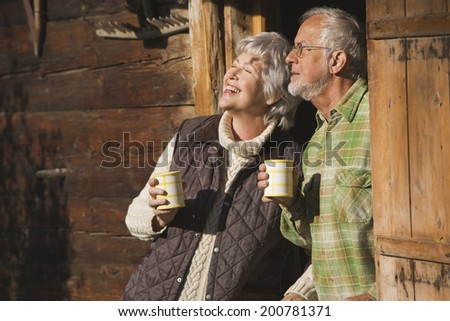 Austria, Karwendel, Senior couple leaning on log cabin's entrance holding mugs - stock photo