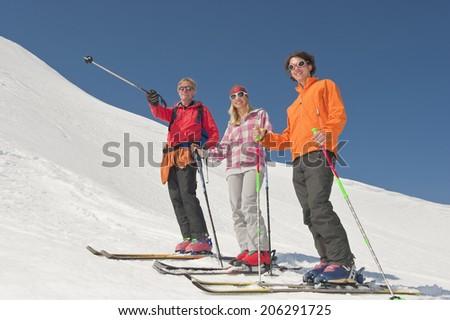 Austria, Salzburger Land, Altenmarkt, Zauchensee, Three persons cross country skiing in mountains - stock photo