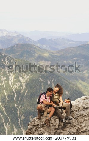 Austria, Salzburger Land, couple consulting map