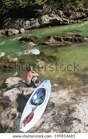 Austria, Salzburger Land, Man sitting on rock with kayak by lammer river - stock photo