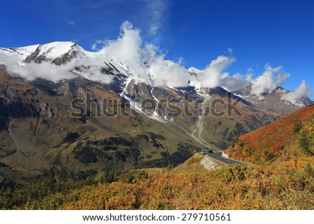 Austrian Alps. Excursion to the picturesque panoramic way Grossglocknershtrasse. Sunny day in early autumn. The mountain slopes are overgrown with grass yellowed - stock photo
