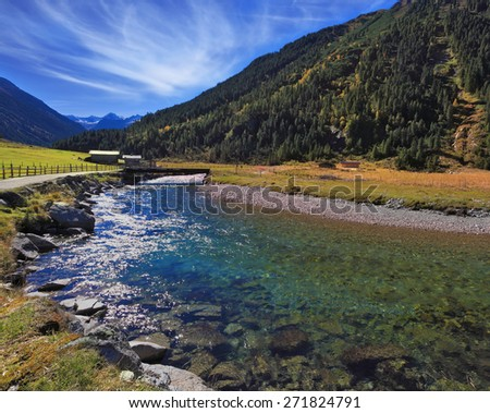 Austrian Alps.  Starting famous Krimml waterfalls. Crystal clear water sparkles in the midday sun. Through the narrow creek wooden bridge spanned - stock photo