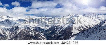 Austrian Alps winter panorama, high mountain view with beautiful clouds and sun - stock photo