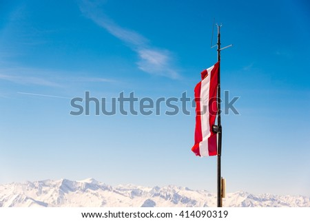 austrian flag fying from an antenna in the alps on a winter day - stock photo