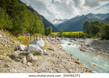 Austrian Tirol Alps landscape with mountains, forests, meadows and brook. - stock photo