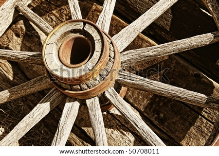 Authentic antique wooden wagon wheel like those used by the pioneers that settled the American Old West – sepia/brown tint and medium depth of field. - stock photo