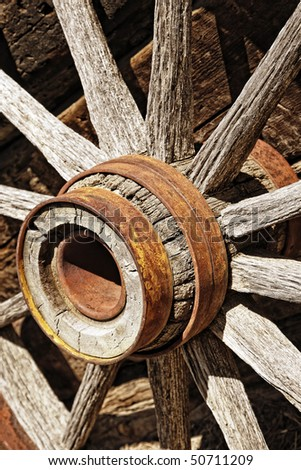 Authentic antique wooden wagon wheel like those used by the pioneers that settled the American Old West – slight sepia/brown tint and medium depth of field. - stock photo