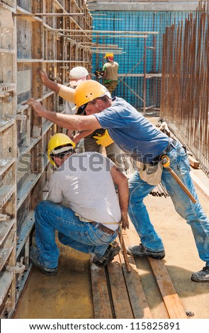 Authentic construction builders working together for positioning concrete formwork frames in place - stock photo