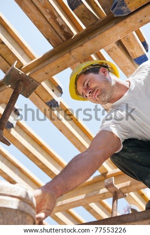 Authentic construction worker bending over under formwork girders to collect a bucket