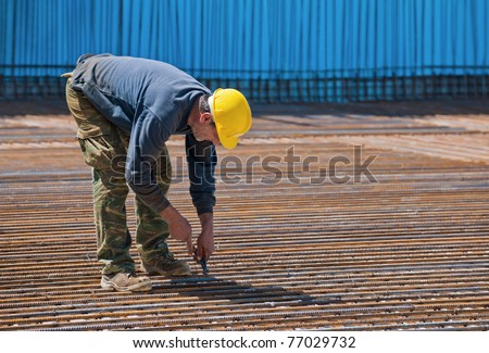 Authentic construction worker installing binding wires to reinforcement steel bars in construction site. Space for text.