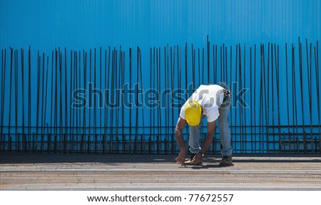Authentic construction worker installing binding wires to reinforcement steel bars in front of a blue insulated surface prior to cement pouring - stock photo