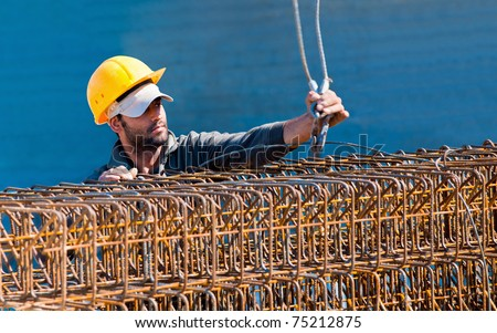 Authentic construction worker loading steel reinforcement stirrup beam cages to a crane hook - stock photo