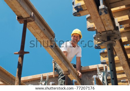 Authentic construction worker placing slab form work beams in construction site - stock photo