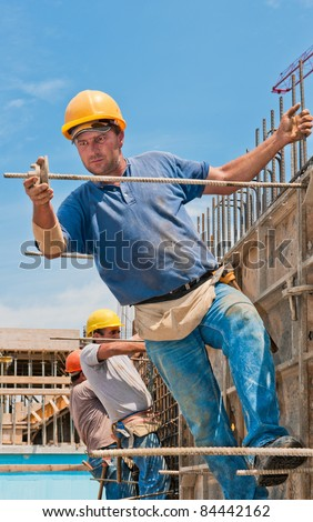 Authentic construction workers installing formwork frames prior to cement pouring - stock photo