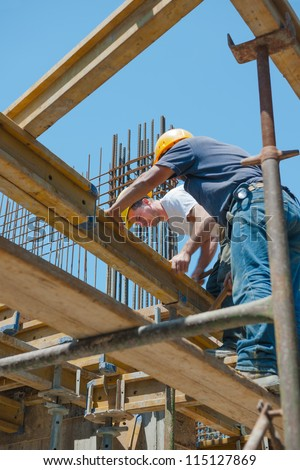 Authentic construction workers placing slab formwork beams in construction site - stock photo