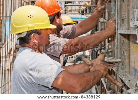 Authentic construction workers positioning in place cement formwork frames - stock photo