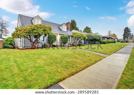 Authentic gray house with large lawn and trees. - stock photo