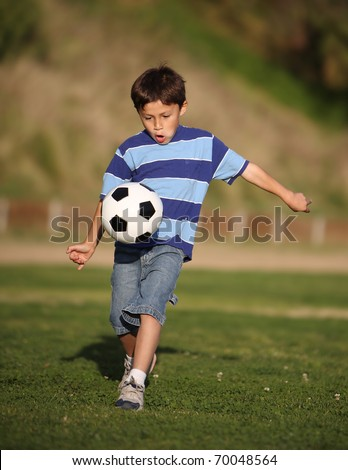 Authentic happy Latino boy playing with soccer ball in field wearing blue striped tee shirt. - stock photo