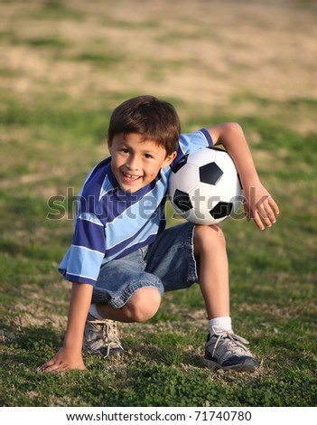 Authentic happy Latino boy with soccer ball in field wearing blue striped tee shirt.