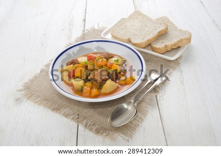 authentic hungarian goulash with beef, bell pepper, potato and carrot and bread on a plate - stock photo