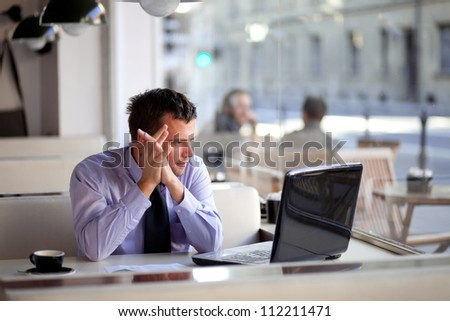 Authentic image of a pensive businessman in a coffee shop - stock photo