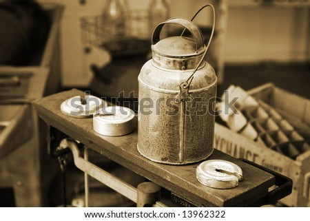 Authentic old-time milk/cream can atop an antique scale with weights in a vintage, historical Creamery setting (vintage tone and grain â?? shallow focus). - stock photo