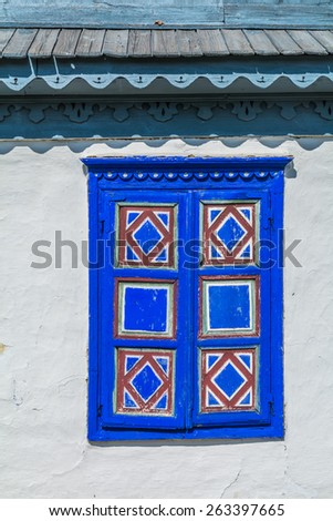 Authentic Romanian village house built with natural bio materials and ancient techniques in traditional architecture. Texture - closeup detail of blue painted window shutter.  - stock photo