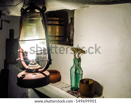 Authentic rustic interior: inside the village hut. Wooden and pottery ware, antique lamp, vases, dried flowers, whitewashed walls. Copyspace for text.
