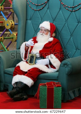 authentic santa clause sitting in large green chair pointing finger
