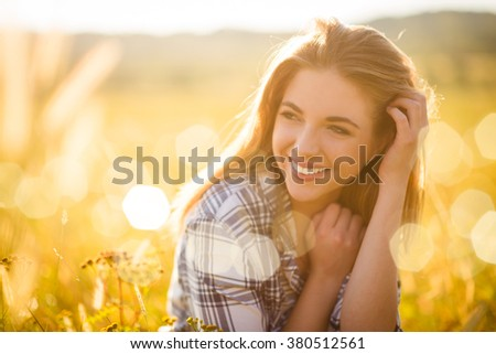 Authentic sunny portrait of young beautiful woman outdoor in nature - stock photo