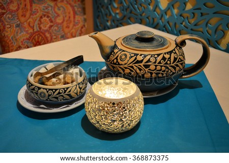 Authentic tea set with handmade mosaic glass candle cup - stock photo