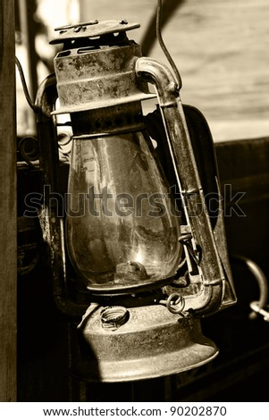 Authentic vintage lantern from American old west era attached to an old wagon (sepia tint added). - stock photo