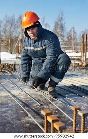 Authentic worker builder positioning and assembling reinforcement rods elements for concrete pouring at construction building area site - stock photo