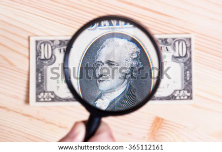 authentication of ten dollars banknote on wooden background