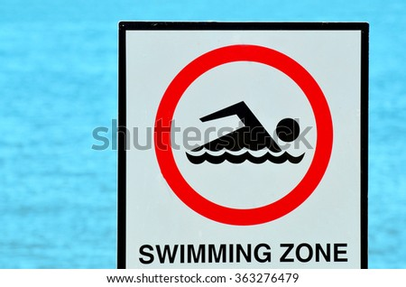 Authorise swimming zone sign against blue water background. - stock photo