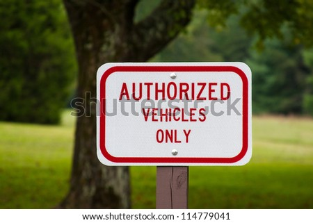 Authorized vehicles only warning sign on a post