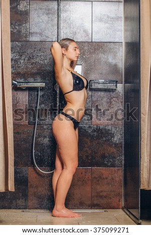autiful woman standing at the shower. In a black bathing suit - stock photo