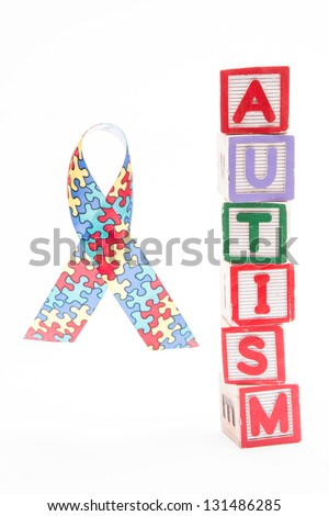 Autism awareness ribbon beside stacked blocks spelling autism on white background - stock photo