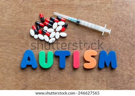 autism colorful word in the wooden background - stock photo
