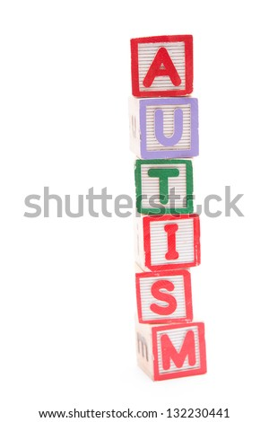 Autism spelled out in stacked letter blocks with copy space on white background - stock photo