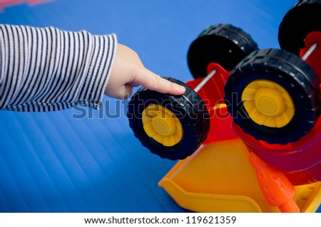 Autistic behavior? Toddler's hand turning wheels on plastic toy. - stock photo