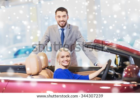 auto business, car sale, consumerism and people concept - happy couple buying cabrio car in auto show or salon over snow effect - stock photo