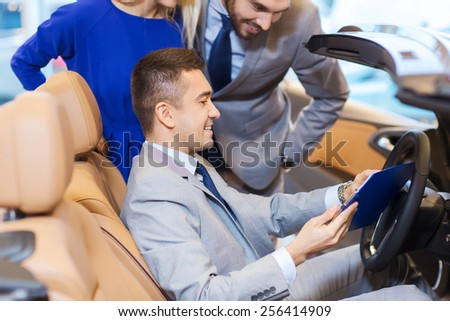 auto business, car sale, consumerism and people concept - happy couple with car dealer in auto show or salon - stock photo