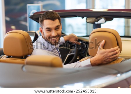 auto business, car sale, consumerism and people concept - happy man sitting in car at auto show or salon - stock photo