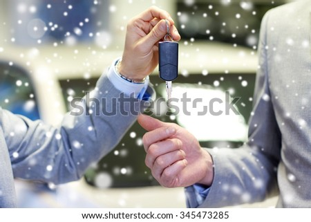 auto business, car sale, deal and people concept - close up of male hands with car key in auto show or salon over snow effect - stock photo
